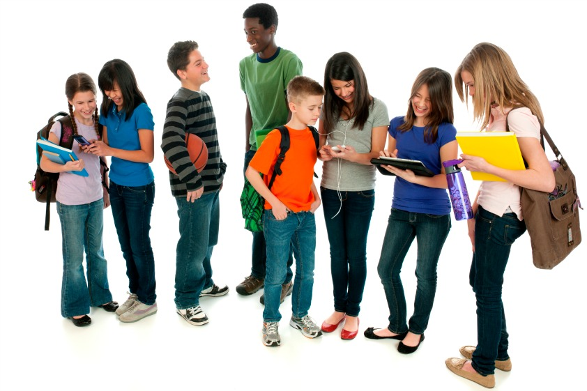 A diverse group of tweens using various electronic devices.